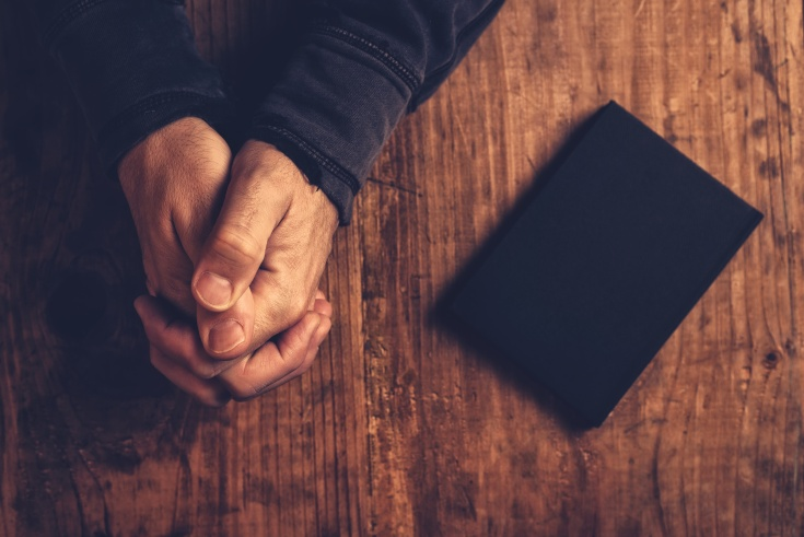 Christian man praying with hands crossed